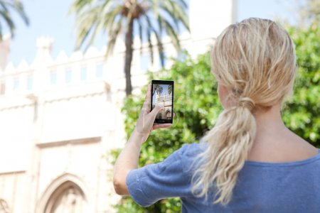 Photo pour Rear portrait view of a young tourist girl holding up a smartphone device to point and take pictures of a monument while visiting a destination city on holiday. Vacation travel and technology networking. - image libre de droit