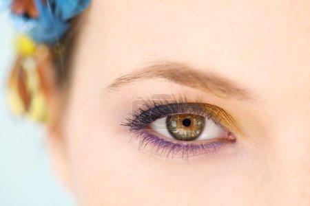 Foto de Retrato de belleza de cerca de una joven media cara con maquillaje azul y amarillo y un vestido de pelo de mariposa sobre un fondo azul, mirando intensamente a la cámara. - Imagen libre de derechos