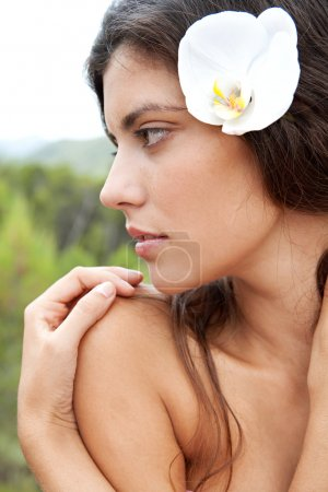 woman elaxing in nature with flower in her hair