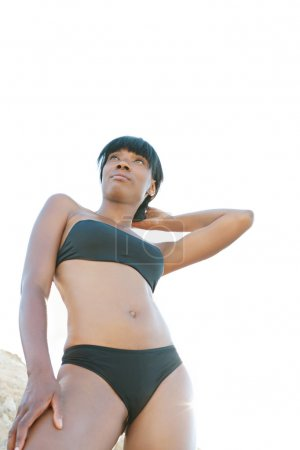 attractive and black woman standing on a beach