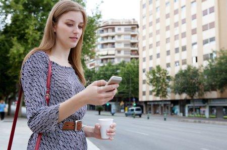 Photo pour Portrait d'une jolie jeune femme d'affaires professionnelle debout dans une rue de la ville tenant et utilisant un smartphone sur le chemin du travail, transportant une tasse de café à l'extérieur. Technologie des entreprises . - image libre de droit