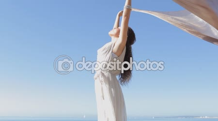 Woman holding and raising a fabric floating in the wind