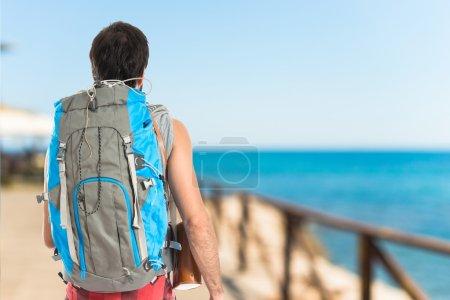 Photo pour Jeune routard marchant sur fond blanc - image libre de droit