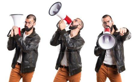 Photo pour Homme portant une veste en cuir criant par mégaphone - image libre de droit