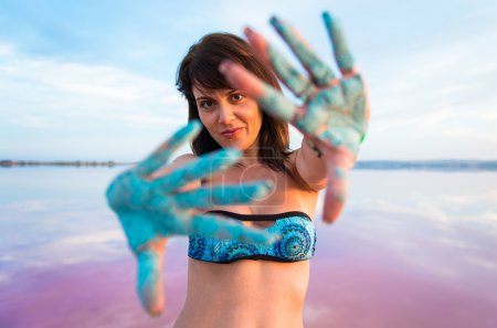 Pretty woman with holi colours in a colorful lake