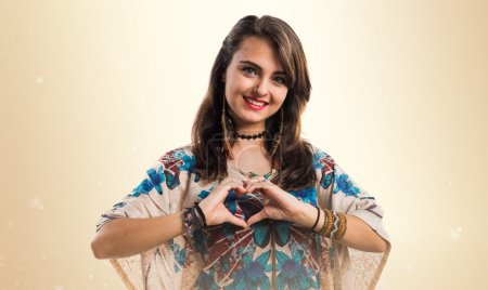 Young girl making a heart with her hands