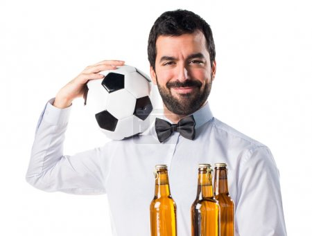 Waiter with beer bottles on the tray holding a soccer ball