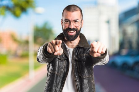 Man wearing a leather jacket pointing to the front