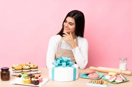 Photo pour Chef pâtissier avec un gros gâteau dans une table sur fond rose isolé regardant sur le côté - image libre de droit