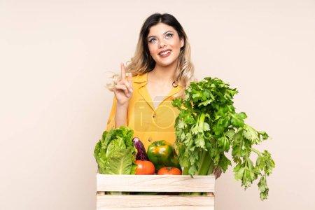Photo pour Adolescente agricultrice avec des légumes fraîchement cueillis dans une boîte isolée sur fond beige pointant avec l'index une excellente idée - image libre de droit