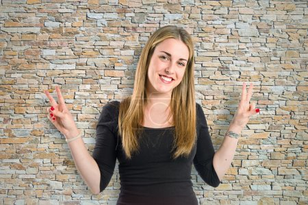 Blonde girl doing victory gesture over textured background