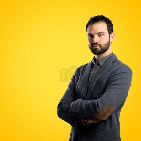 Geschäftsmann mit verschränkten Armen vor gelbem Hintergrund