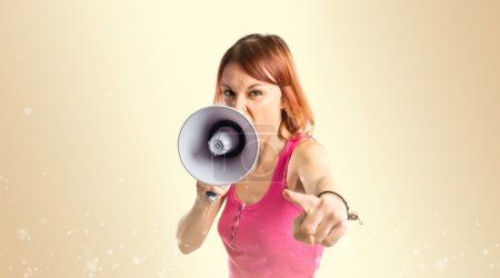 Redhead girl shouting with a megaphone over ocher background