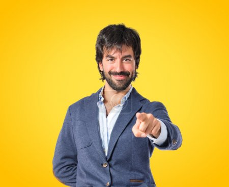 Man pointing to the front over yellow background