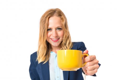 Blonde girl holding a cup of coffee over white background