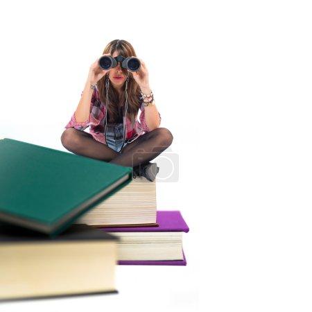 Photo pour Fille avec des jumelles assis sur des livres - image libre de droit