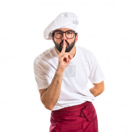 Chef making silence gesture over white background