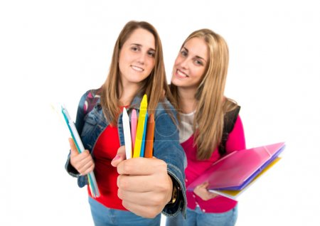 Students holding crayons over white background