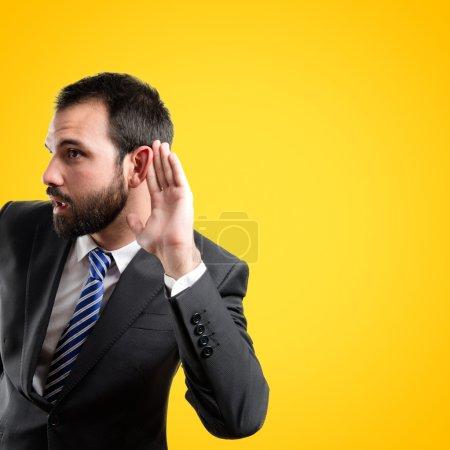 Photo pour Homme d'affaires jeune entendre quelque chose sur fond jaune - image libre de droit
