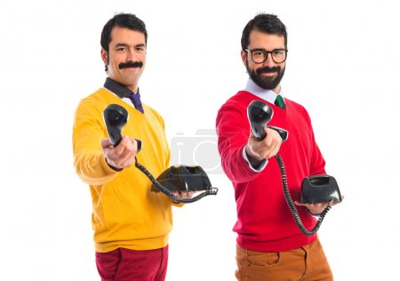 Twin brothers holding vintage phone