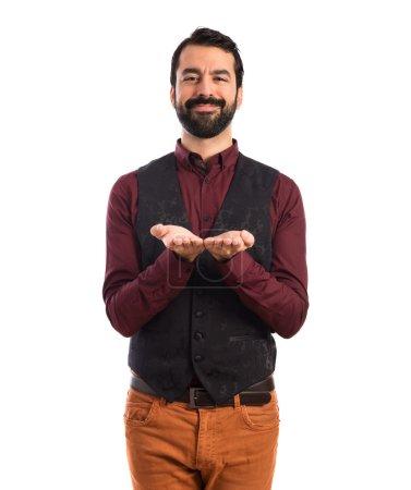 Man wearing waistcoat holding something