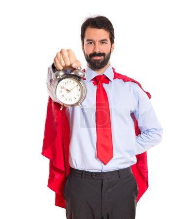 Homme d'affaires, vêtu comme super-héros tenant une horloge