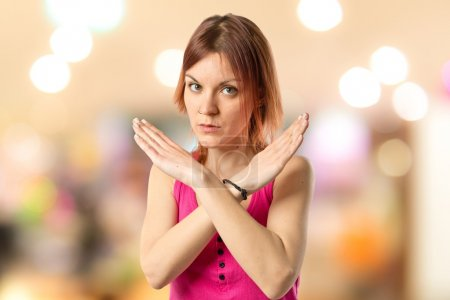 Redhead girl doing NO gesture over white background