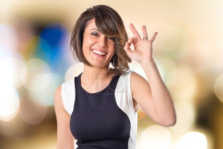 Pretty woman making Ok sign over white background