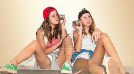 Photo pour Amis avec leurs planches à roulettes parler à travers un téléphone en étain - image libre de droit