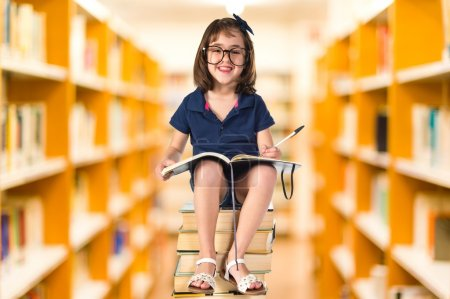 Photo for Girl studying on a pile of books - Royalty Free Image