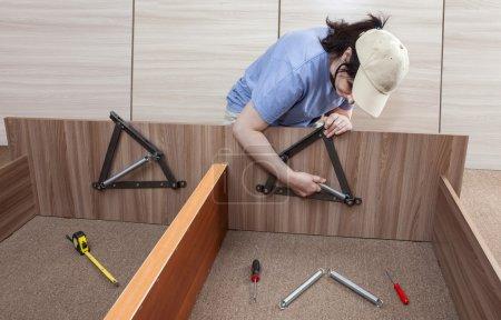 Photo pour Auto montage meubles à la maison, femmes, assembler des meubles d'auto-assemblage, assembler système mécanisme de levage réglable lit cadre printemps. - image libre de droit