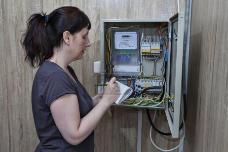Woman checking electric counter, standing near electricity switchgear indoors.