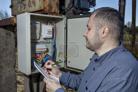 Electric substation, Technician Writing Reading Of electricity Meter On Clipboard.
