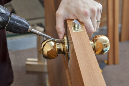 Photo for Install the door handle with a lock, Carpenter tighten the screw, using an electric drill screwdriver, close-up. - Royalty Free Image