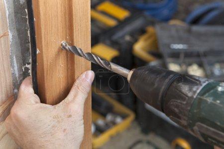 Photo pour Installation de portes intérieures, gros plan d'une perceuse électrique perçant un trou dans le montant du cadre en bois. - image libre de droit