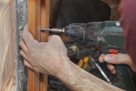 Photo pour Jambage de fix de charpentier en porte avec un tournevis électrique perceuse sans fil, gros plan. - image libre de droit