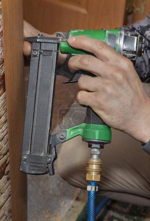 Photo pour Installation de la porte, close-up main tenant le pistolet Agrafeuse pneumatique, fixation boîtier au cadre de porte. - image libre de droit
