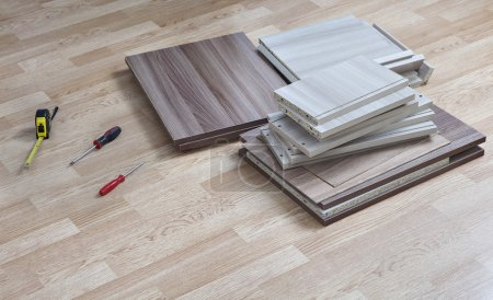 Photo pour Meubles de paquet plat couché sur le sol lors de la prochaine maison à portée de main des outils pour l'assemblage. - image libre de droit