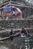 Two asian women rinse the laundry in river village, China.