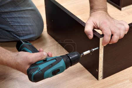 Woodworker Assembling Furniture made of chipboard using a cordless screwdriver.