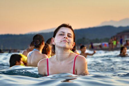 Young Caucasian girl bathes in the sea evening