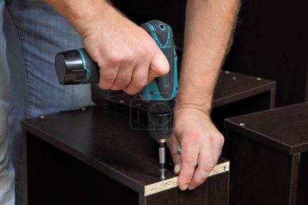 Hands carpenter with screwdriver, tighten screw in drawers of chipboard.