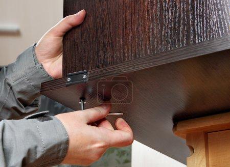 Allen furniture key in hand, fastens screw, close-up.