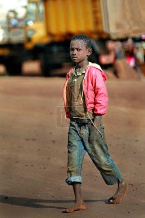 Dark skinned African boy walking barefoot in dirty jeans.