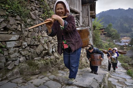 Asian farmers climb up mountain trail, with load on shoulders.