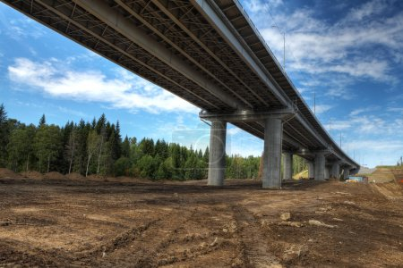 Bottom view on steel highway bridge spans on concrete supports.