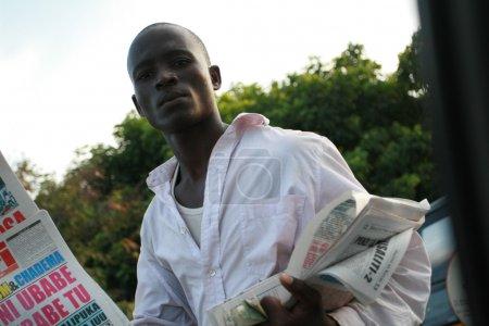 Молодых африканских мужчин, предлагает гостям газеты водителям в пробке