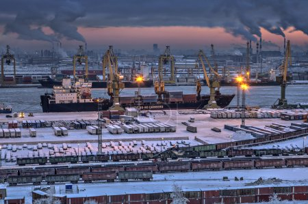 Unloading of cargo ship in sea port winter evening.