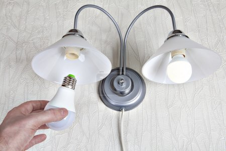 Replacing the bulbs in wall lights, hand holds  LED lamp.
