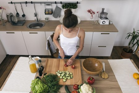 Photo for Young woman cutting vegetables for salad in modern kitchen - Royalty Free Image